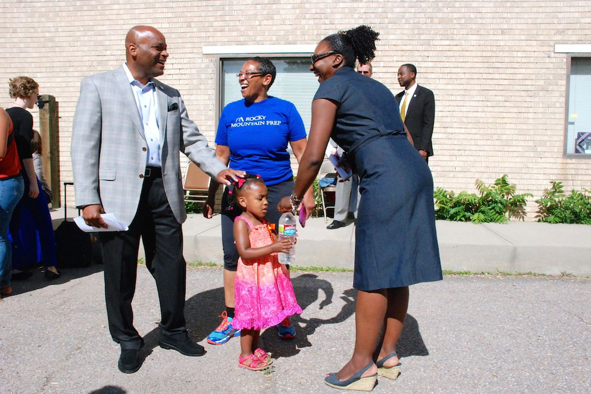 Denver Mayor Michael Hancock, left, speaks with Monica Moore, center, and Marshall Fox and her daughter Kennedy June 11 at the Hope Center Children's Program in northeast Denver. The mayor announced a campaign to renew and raise a sales tax to fund the Denver Preschool Program.