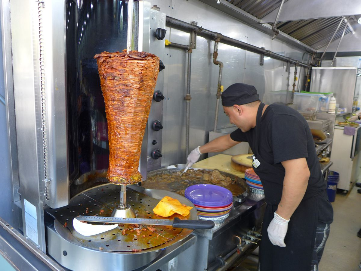 A man saws away at the al pastor meat cylinder