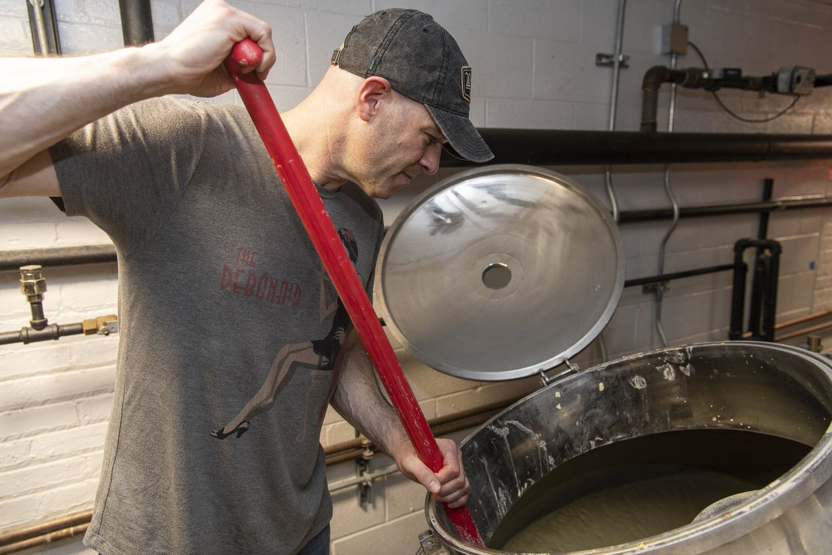Eric Falberg stirring mash at 28 Mile Distillery., Monday, March 23, 2020, in Highwood Ill. This batch of mash is a combination of corn and barley and will be used to distill alcohol for hand sanitizer. | Tyler LaRiviere/Sun-Times
