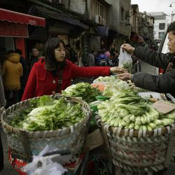 In this March 20, 2012 photo, a customer buys vegetable from a street vender in Shanghai, China. China's inflation edged up in March as the government shifted focus from containing politically dangerous price rises to stimulating its slowing economy. Consumer prices rose 3.6 percent over a year earlier, up from February's 3.2 percent, data showed Monday, April 9, 2012.