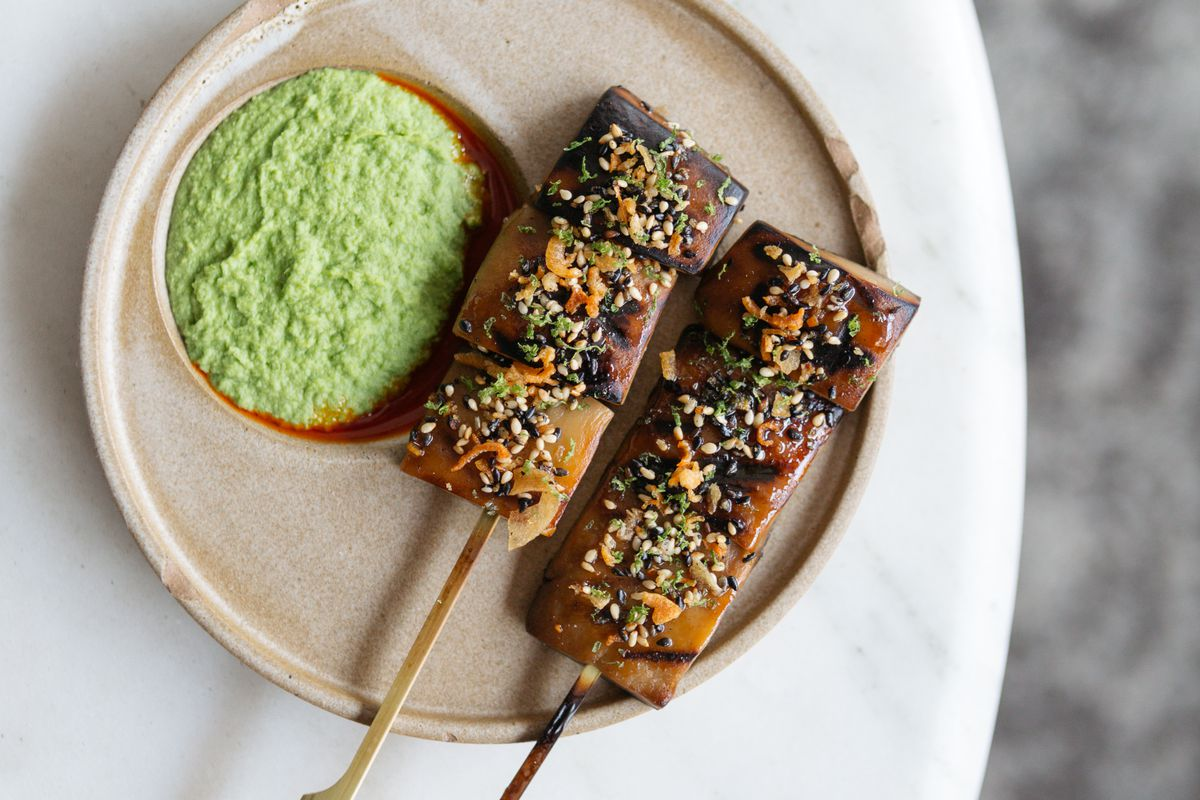 Two skewers with blocks of brown-ish food with sprinkled seeds next to a saucer of light green sauce on a beige plate which is on a white table.