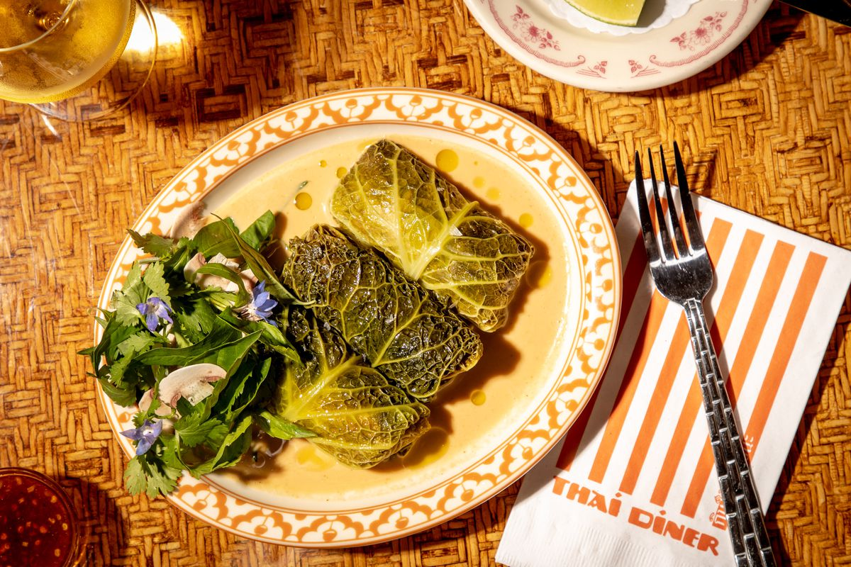 Green stuffed cabbage rolls sit atop a pool of coconut milk on a patterned white plate next to a striped orange and white napkin