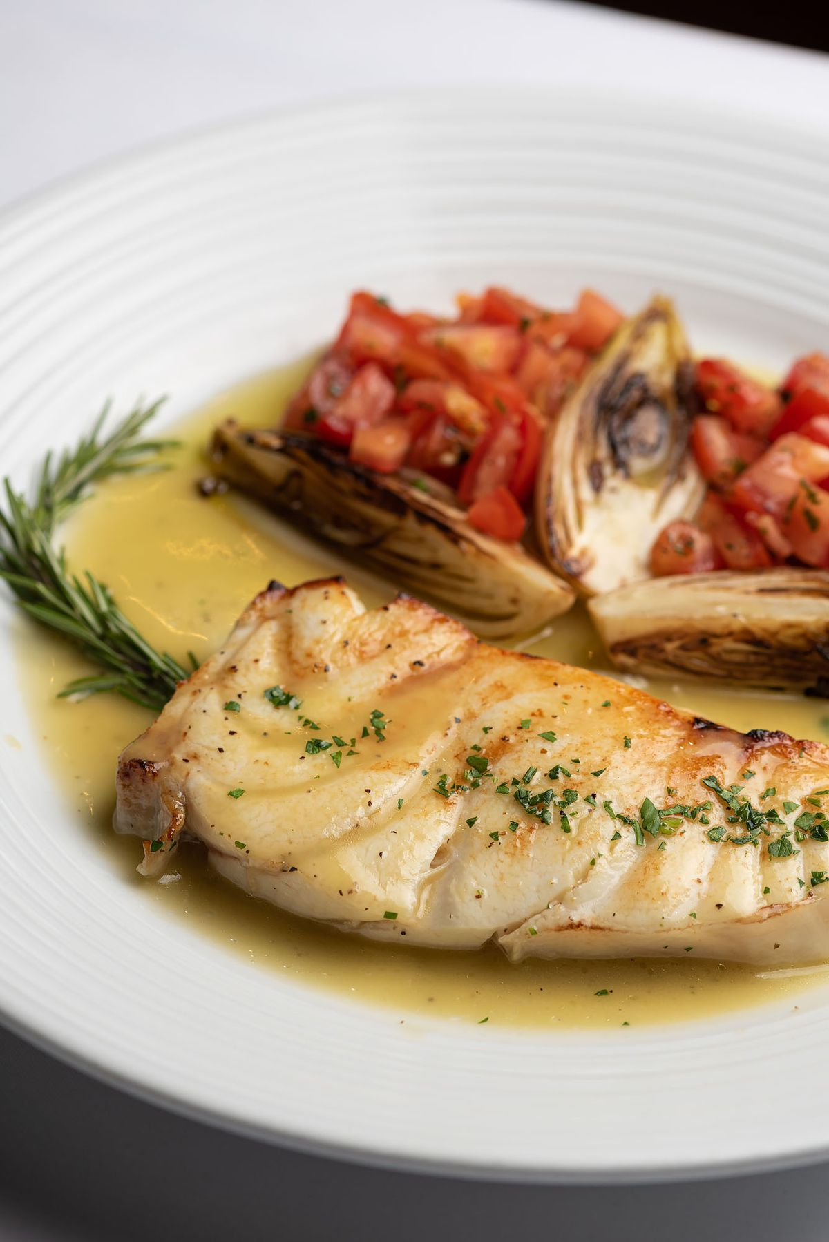 A cooked white fish in butter with tomatoes and artichoke on the side.