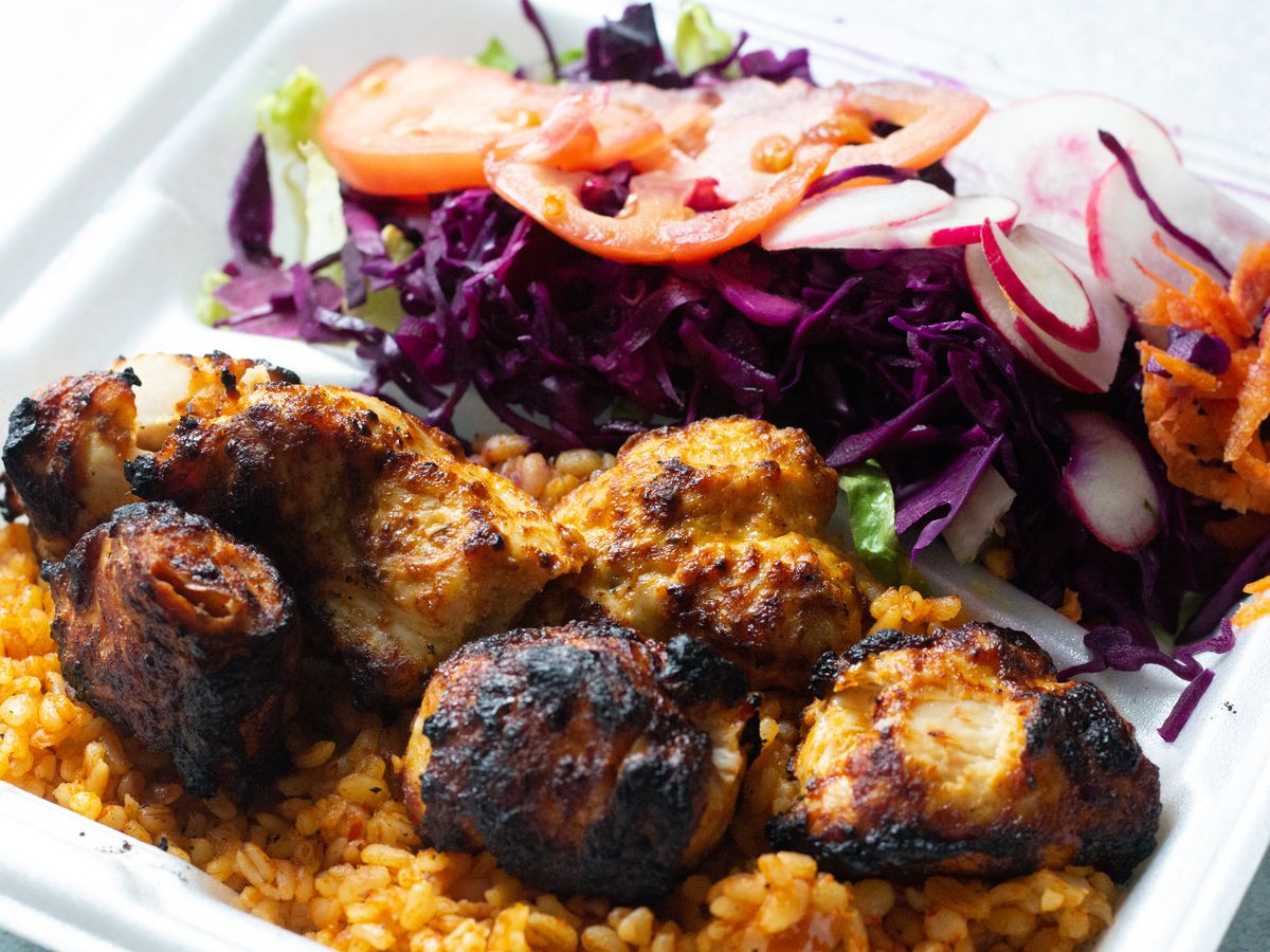 Charred chunks of chicken sit on red bulgur next to a side salad, all in a white styrofoam container