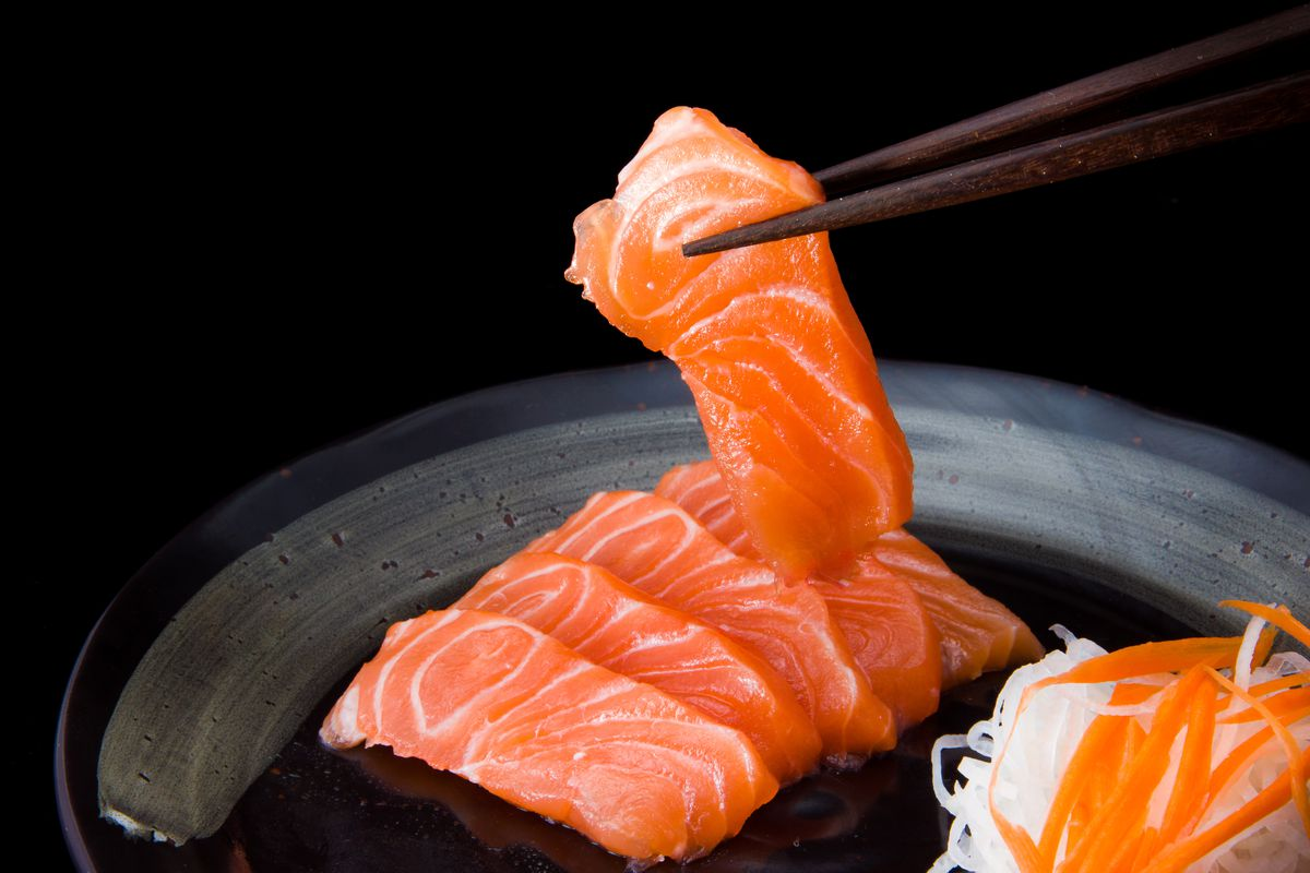 Salmon sashimi served on a black plate. A chopstick is picking up one slice.