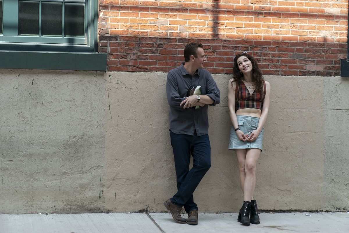 Simone and Peter lean against a brick wall.