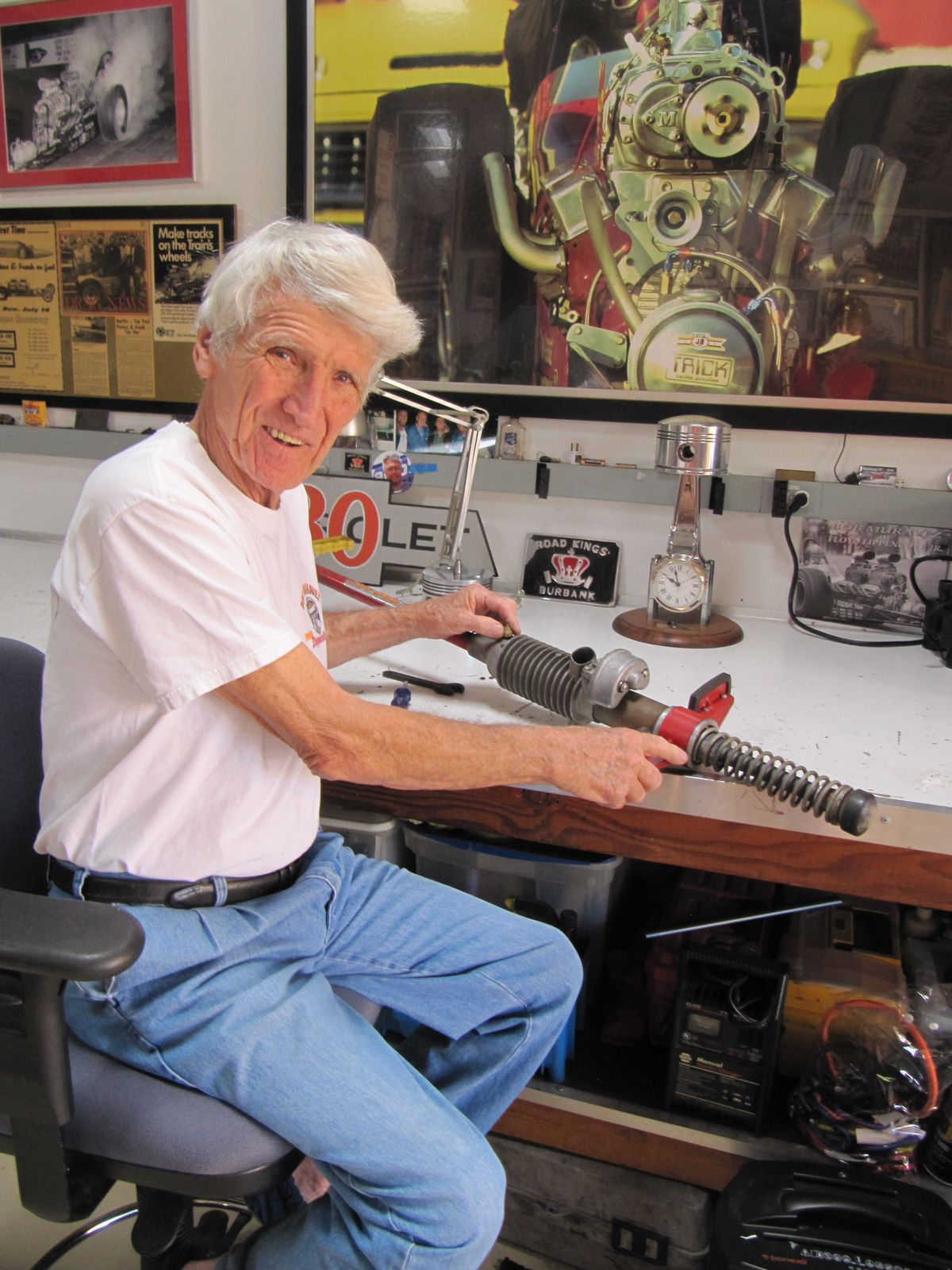 Color photo of Bob Muravez in his garage in 2020 — white hair, white t-shirt, light blue jeans. He is sitting at a work table, showing off a hot rod suspension and smiling.