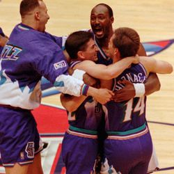 Utah Jazz's Karl Malone, center, hugs teammates Jeff Hornacek (14) and John Stockton (12) as Greg Foster, left, joins in the celebration after the Jazz beat the Rockets 103-100 in Game 6 of the Western Conference Finals Thursday, May 29, 1997, in Houston. Stockton hit a three-pointer at the buzzer for the Jazz victory. The Utah Jazz will now play the Chicago Bulls in The NBA Finals. (AP Photo/David J. Phillip)