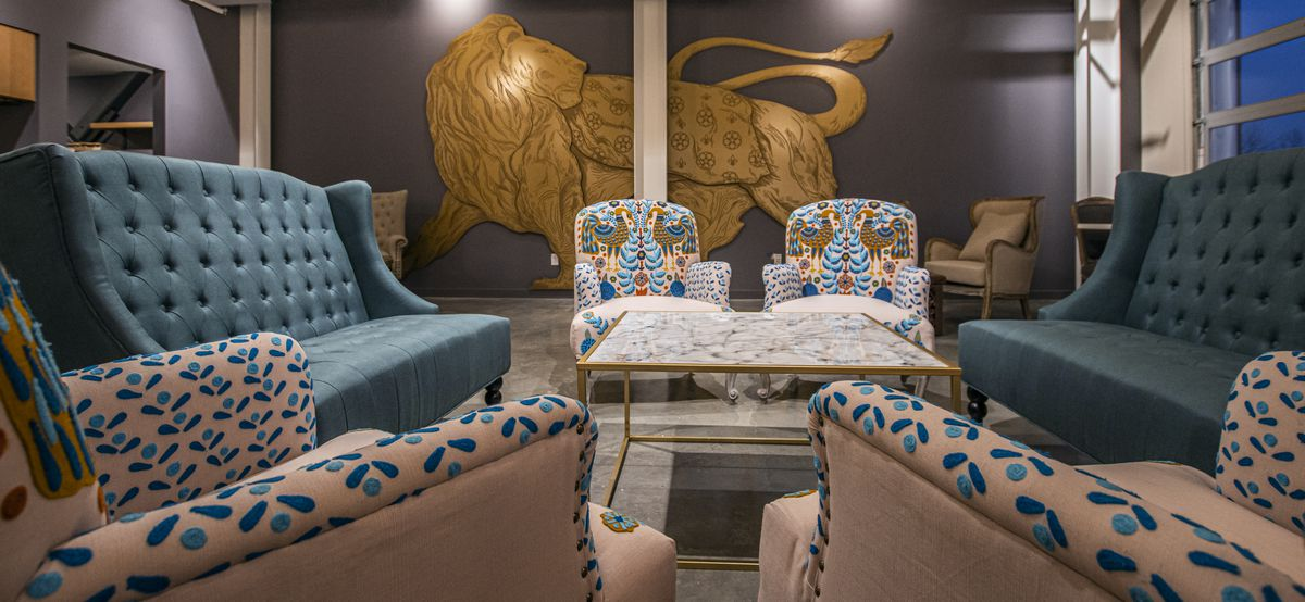 A lounge with colorful vintage couches and a lion mural.