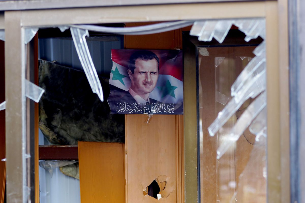 A picture taken on February 9, 2016, shows, through a broken window, a portrait of Syrian President Bashar al-Assad hanging on a wall in a building next to the site of a suicide attack at a police officer's club in Damascus.