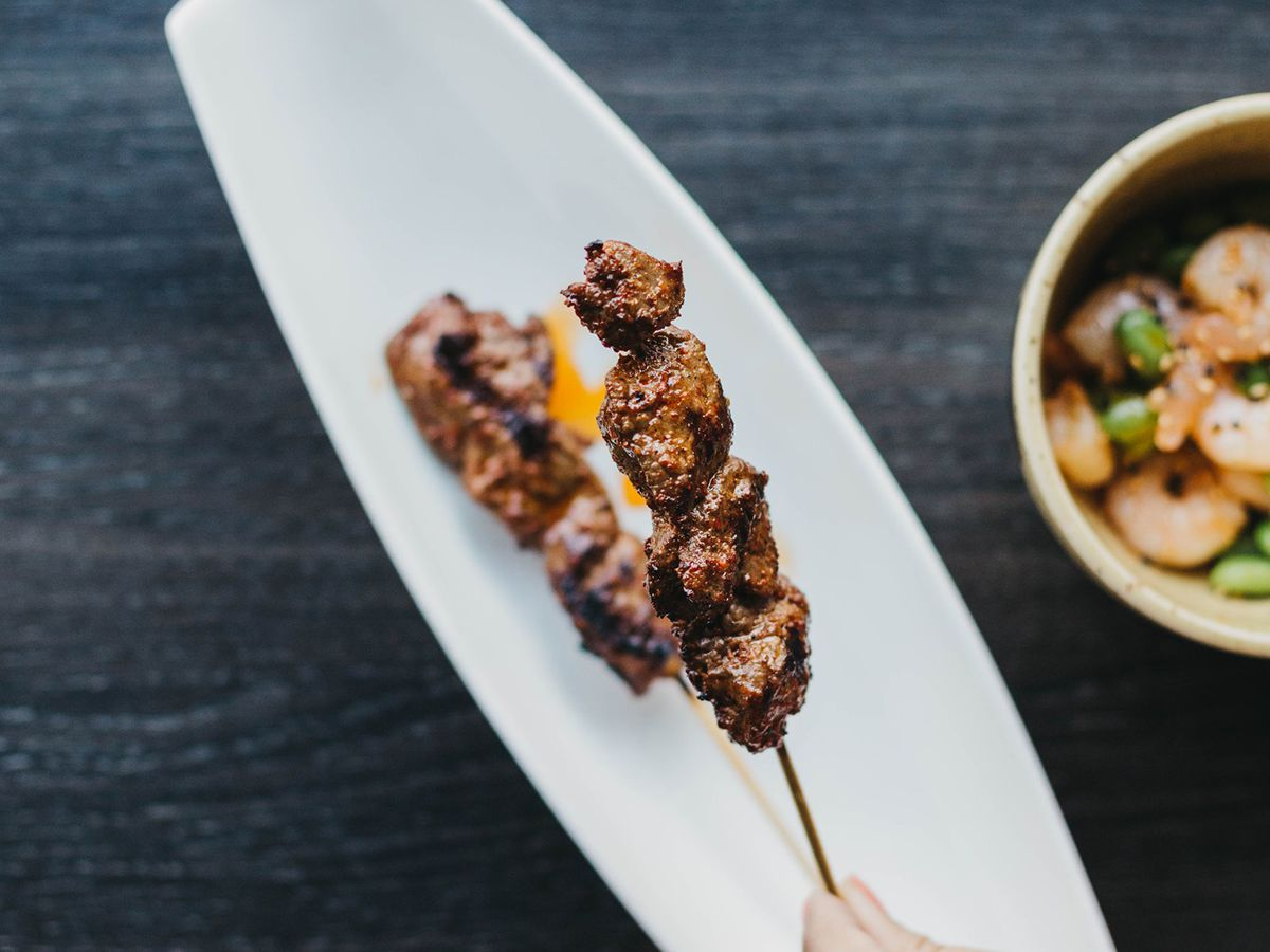 A hand holds a yakitori skewer over a white plate.
