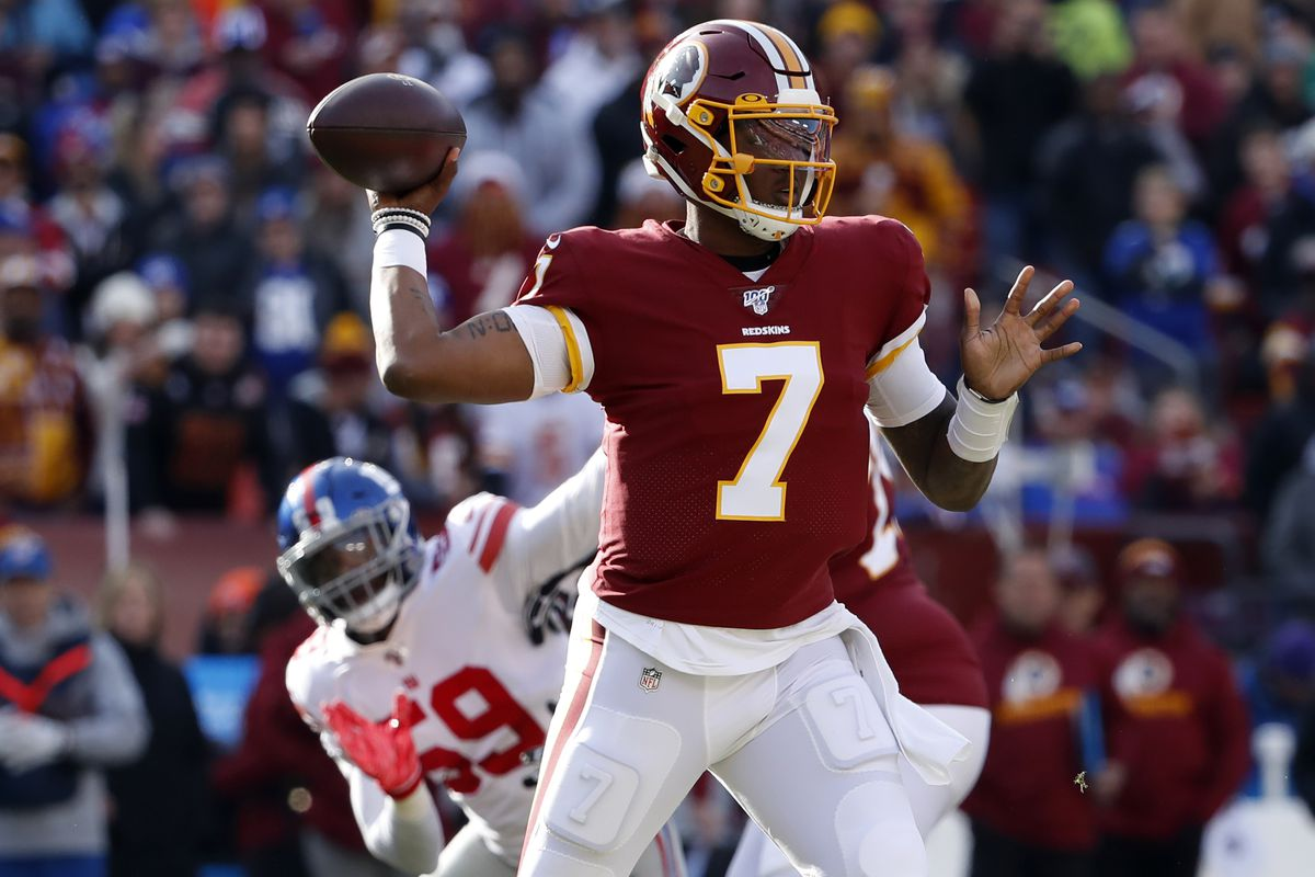 Washington quarterback Dwayne Haskins passes the ball as New York Giants linebacker Lorenzo Carter chases in the first quarter at FedExField.