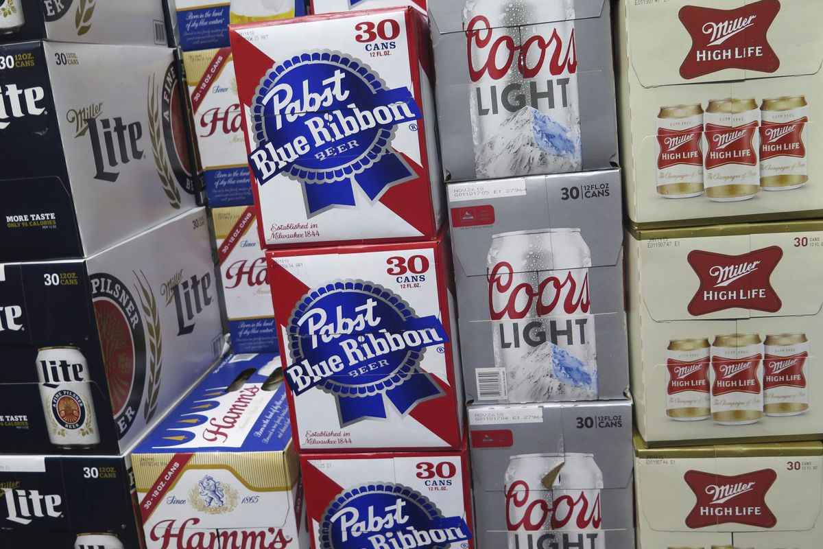 FILE - In this photo taken on Thursday, Nov. 8, 2018, cases of Pabst Blue Ribbon and Coors Light are stacked next to each other in a Milwaukee liquor store.