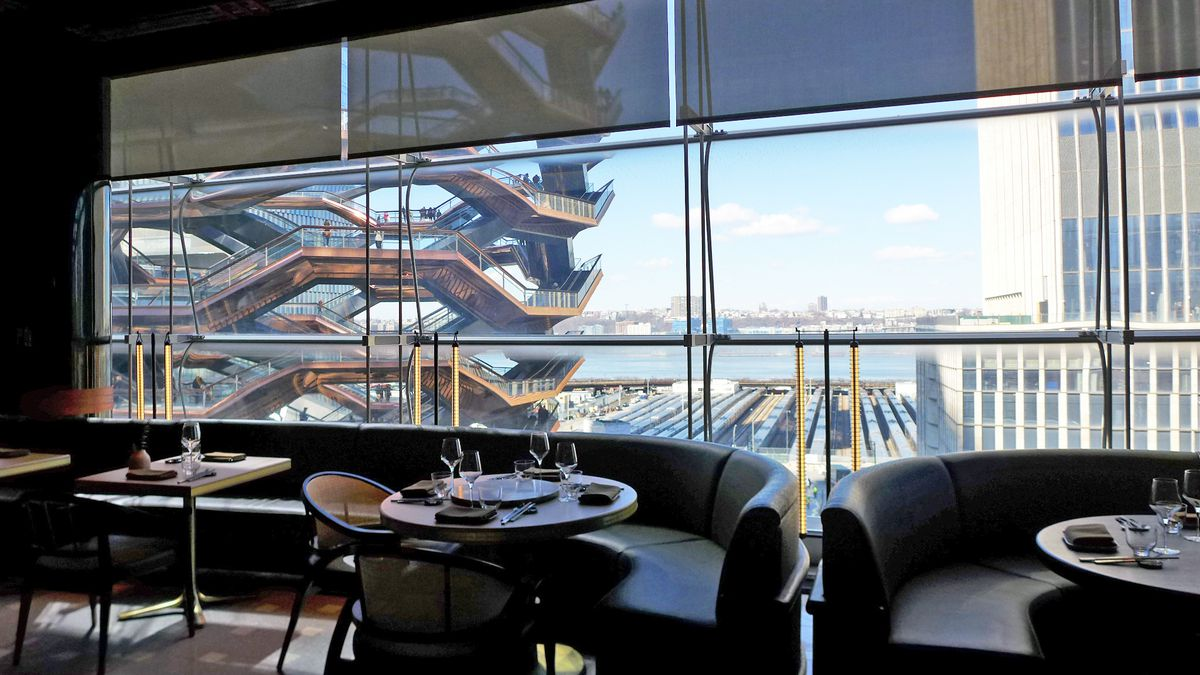 View out the windows of Hudson Yards includes the giant helical structure called Vessel, and the Jersey shore in the background.