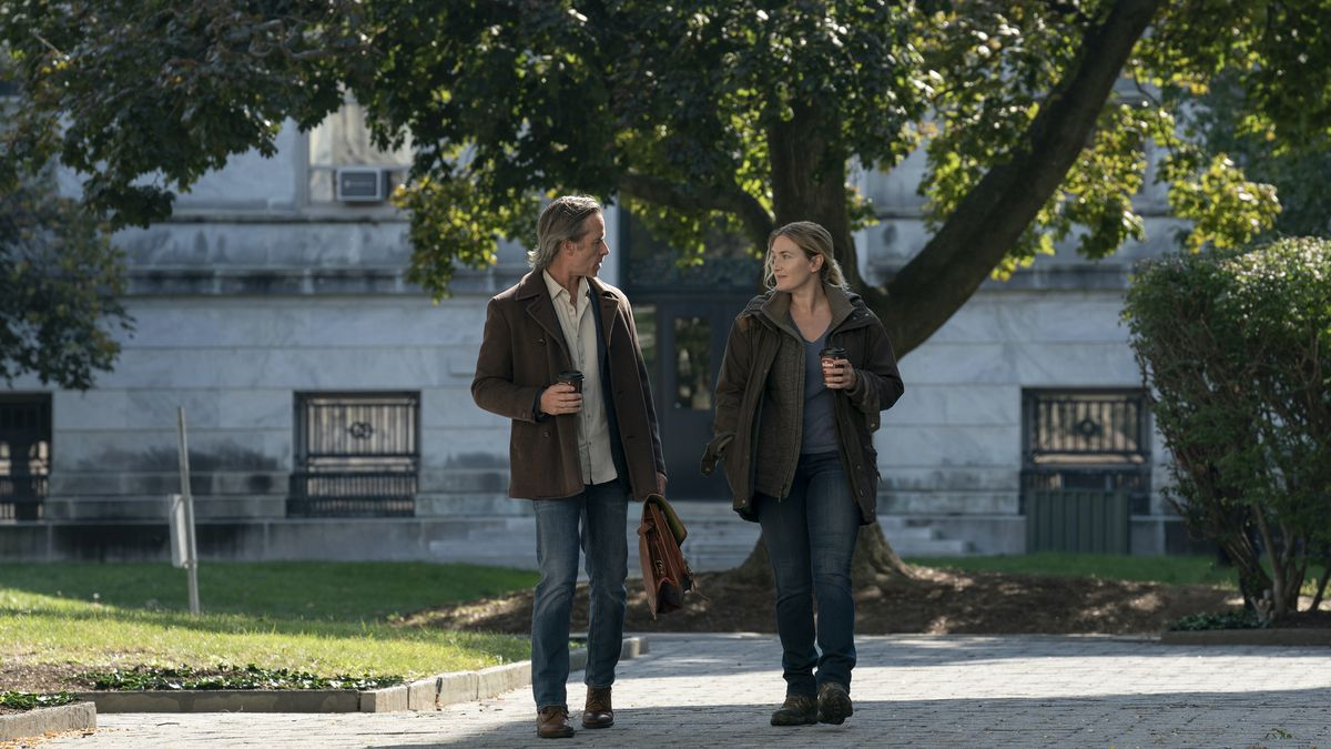 guy pearce and kate winslet walk on a college campus holding wawa coffees