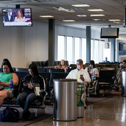 People sit at a gate, some wearing masks and others not, at Salt Lake City International Airport on Thursday, April 30, 2020. Like airports all over the world, Salt Lake's airport has seen air traffic plummet due to the COVID-19 pandemic.