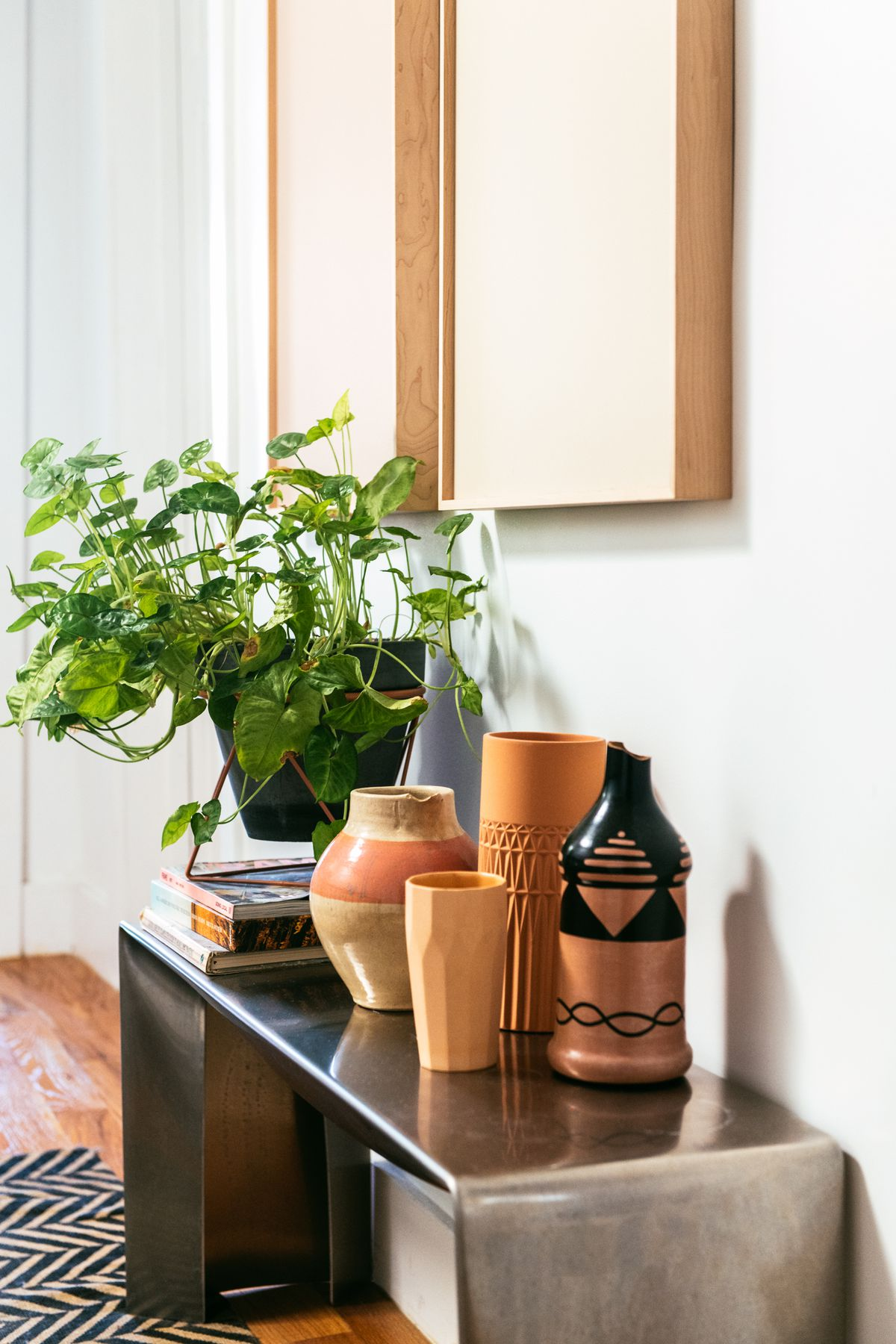 A metal bench sits against a painted white wall. There are assorted ceramics and a houseplant in a planter on the bench. There is a patterned black and white area rug on the floor.