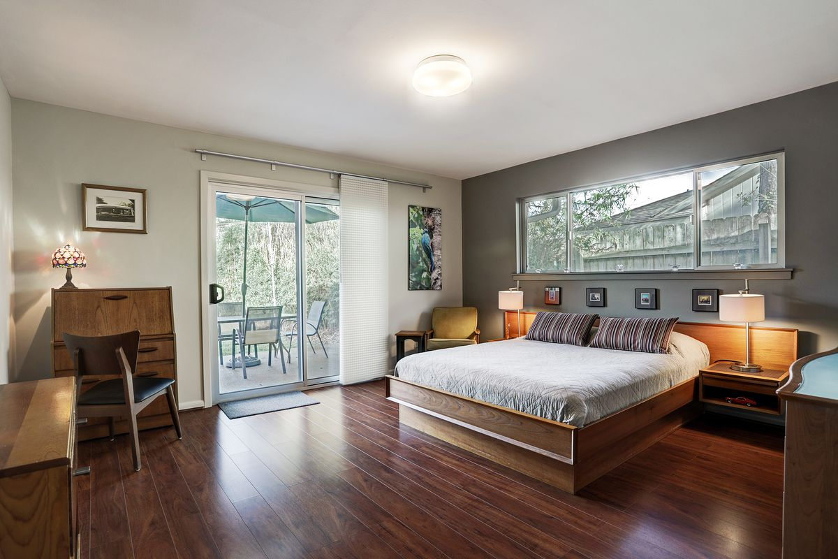 A master bedroom has a wooden platform bed with white linens, a gray accent wall, and a sliding glass door to the backyard.