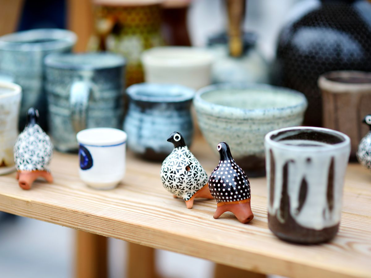 A wood shelf full of glazed ceramic objects, including drinking cups, bowls, and two small statues of birds.