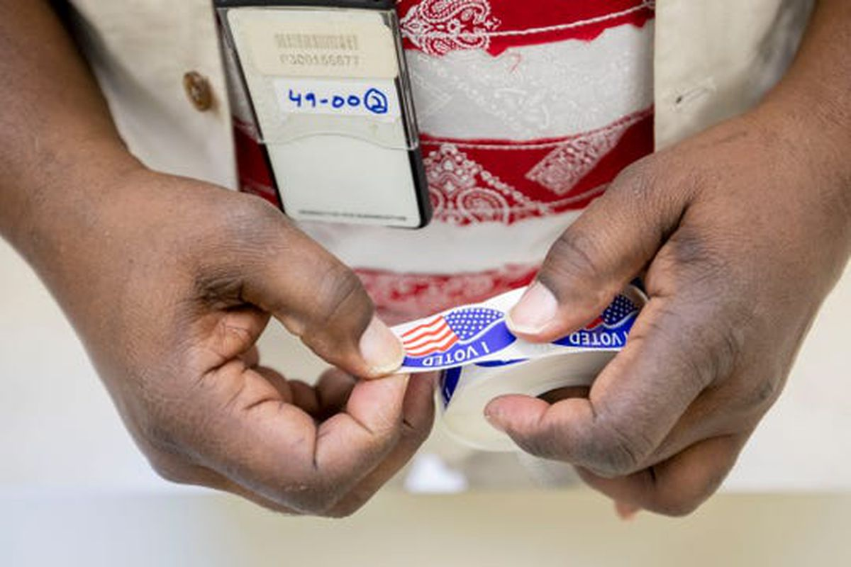 Poll worker Wardell Chambers tears stickers Tuesday, March 3, 2020, while voting at Pine Hills Community Center in Memphis.