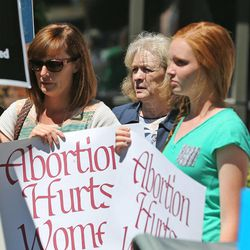 Gayle Ruzicka, leader of Utah Eagle Forum, stands in the background as a group called Women Betrayed holds a rally to support ending taxpayer funding of Planned Parenthood in front of the Planned Parenthood offices, July 28, 2015, in Salt Lake City.