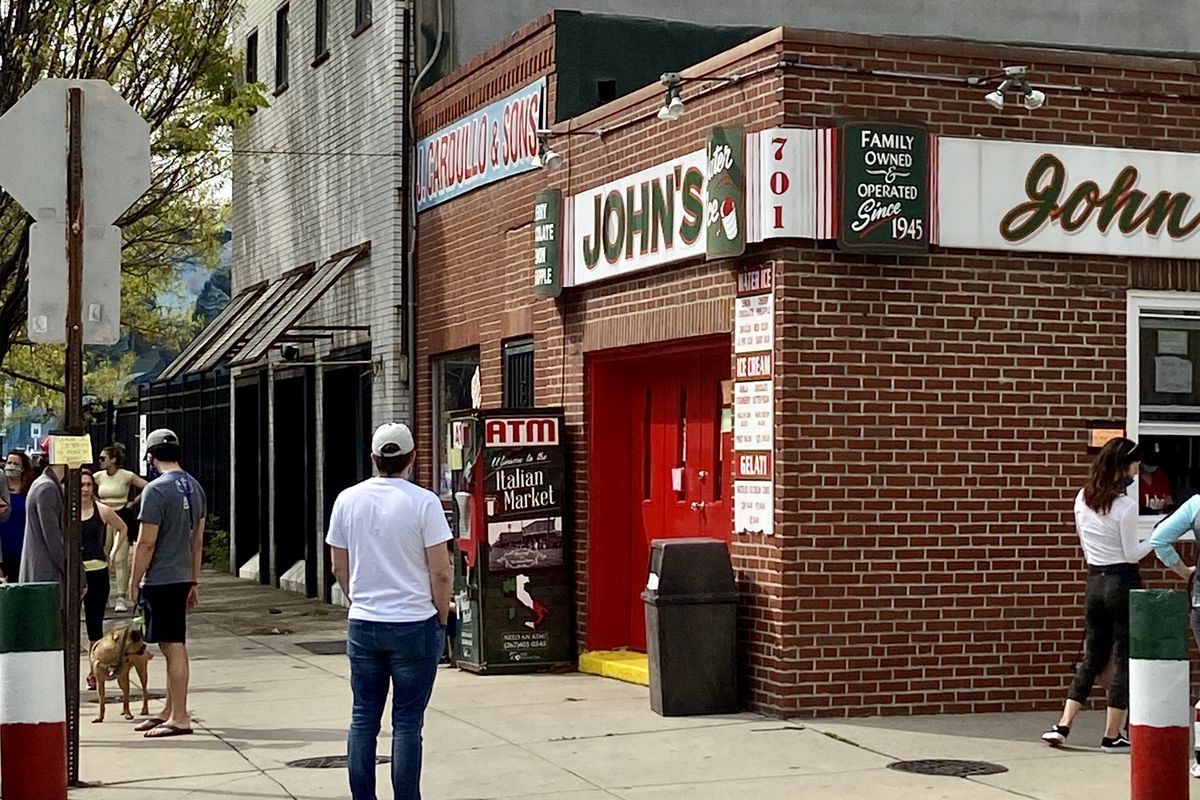 people in line for takeout window at corner venue with a sign that says john's