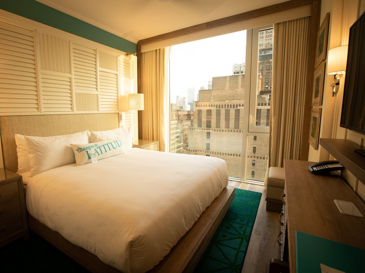 A hotel room with a bed overlooking the city.