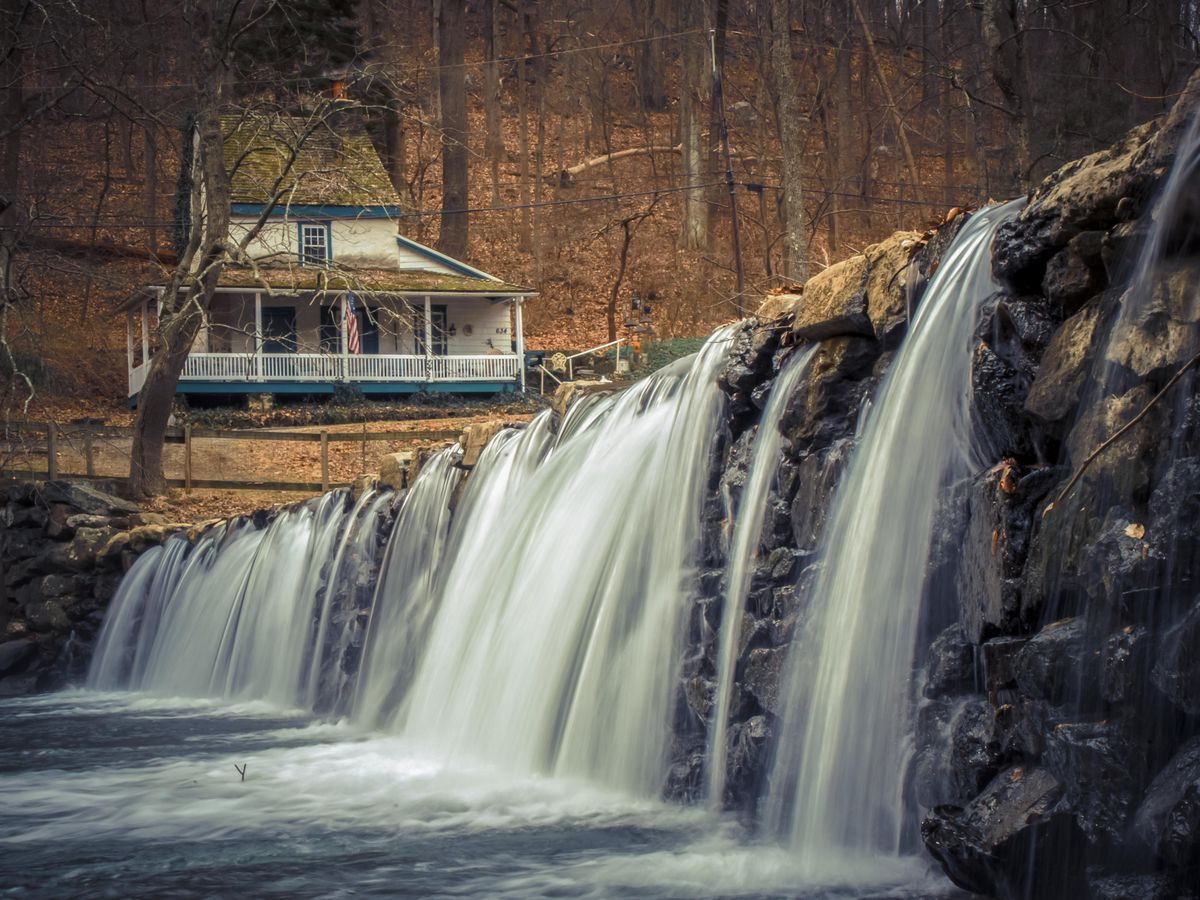 In the foreground is a waterfall on a rock face. In the distance is a house surrounded by trees. There are fallen autumn leaves on the ground.