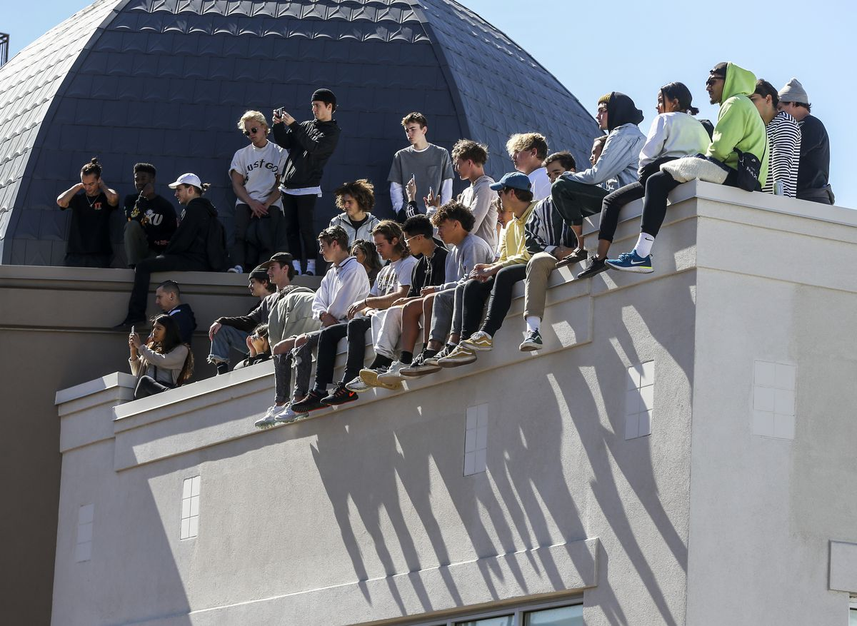 """Spectators sit on a roof at The Gateway mall in Salt Lake City for Kanye West's """"Sunday Service"""" on Saturday, Oct. 5, 2019. Thousands packed into the outdoor mall causing people to stand on and climb up anything they could find to catch a glimpse of West. Residents in the nearby apartment complex were complaining of trespassers."""
