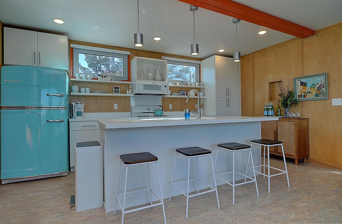 A kitchen has white cabinets, counters, and four counter-height stools.