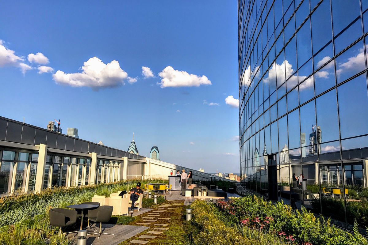 An outdoor lounge area in the FMC Tower in Philadelphia. There are couches, chairs, and tables. There is a path with stones. There are flower beds.