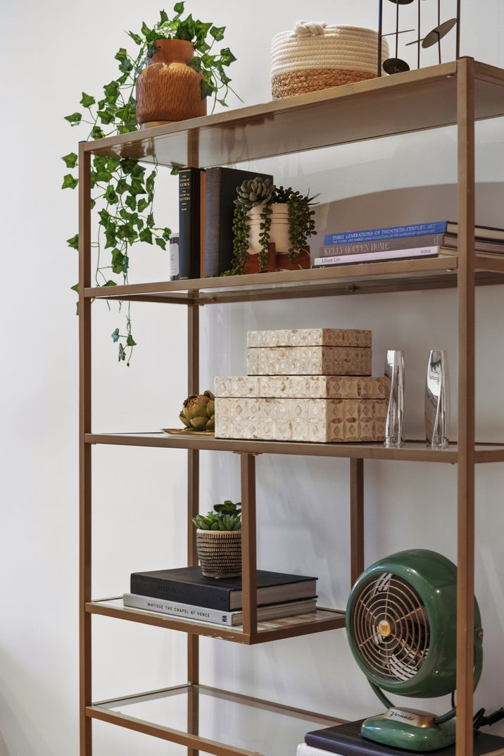A wooden shelf with several objects and a planter.