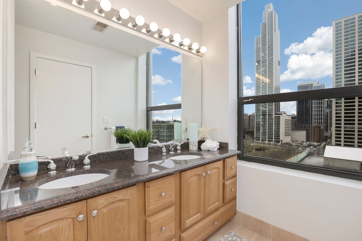 A double vanity sink in front of a large mirror. Tall buildings and a park can be seen out the window.