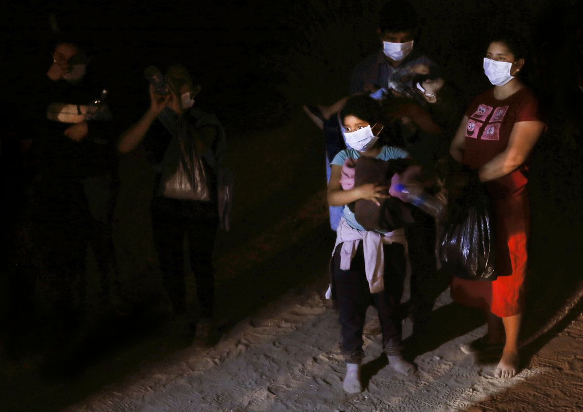 A group of undocumented migrants from Guatemala and and El Salvador seeking asylum are detained near the border wall in McAllen, Texas, on Tuesday, June 22, 2021.