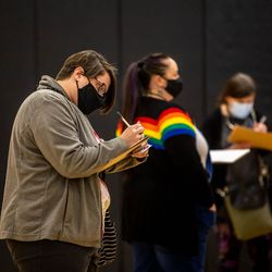 People fill out forms as the Canyons School District holds its final COVID-19 vaccination clinic at Mount Jordan Middle School in Sandy on Thursday, March 11, 2021.