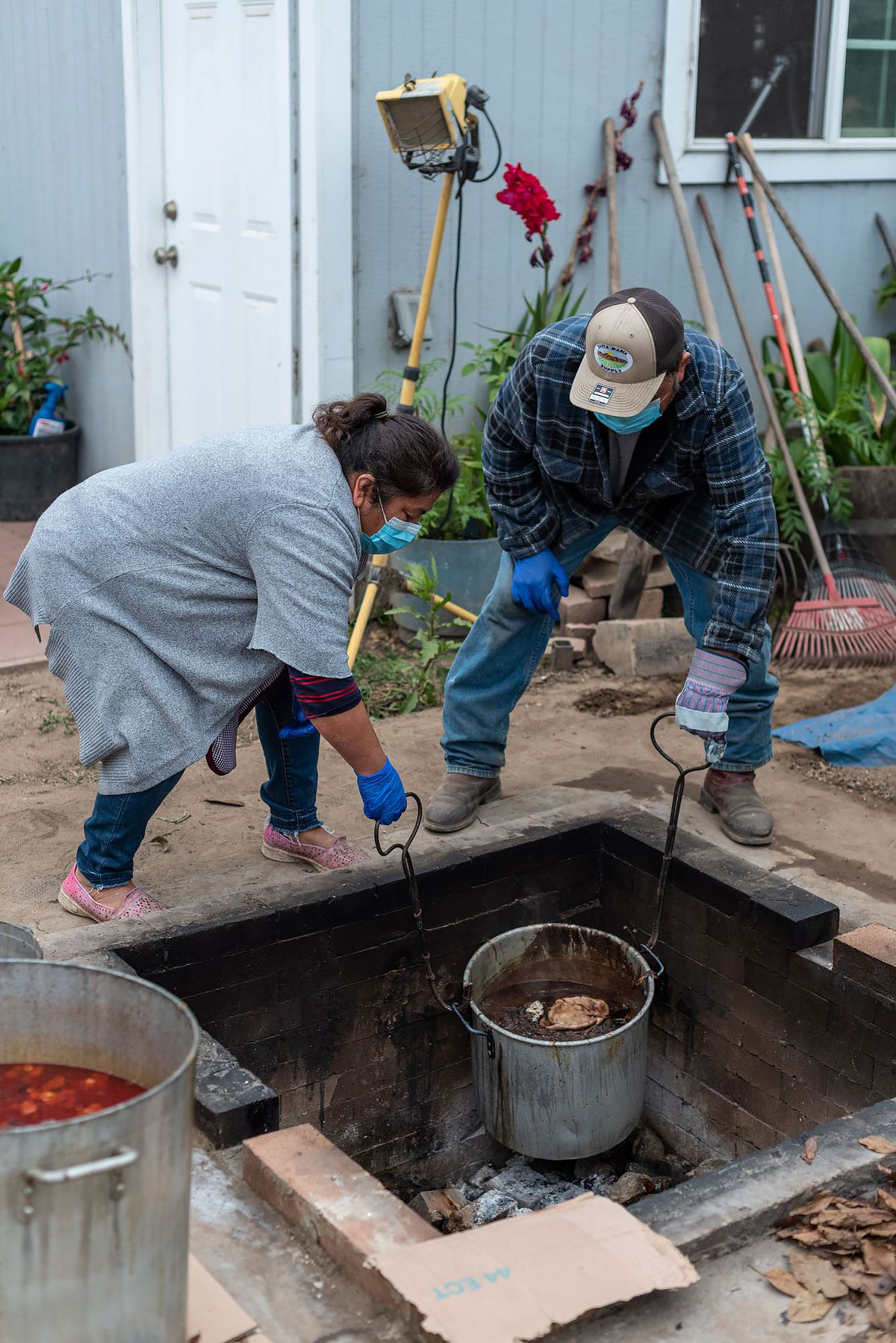 The Bautistas take out a pot of loose blood sausage from their barbacoa pit.