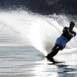 A lone waterskier enjoys making turns over smooth water. Water skiing is just one of the water sports possible at Lake Powell, August 10, 2009.