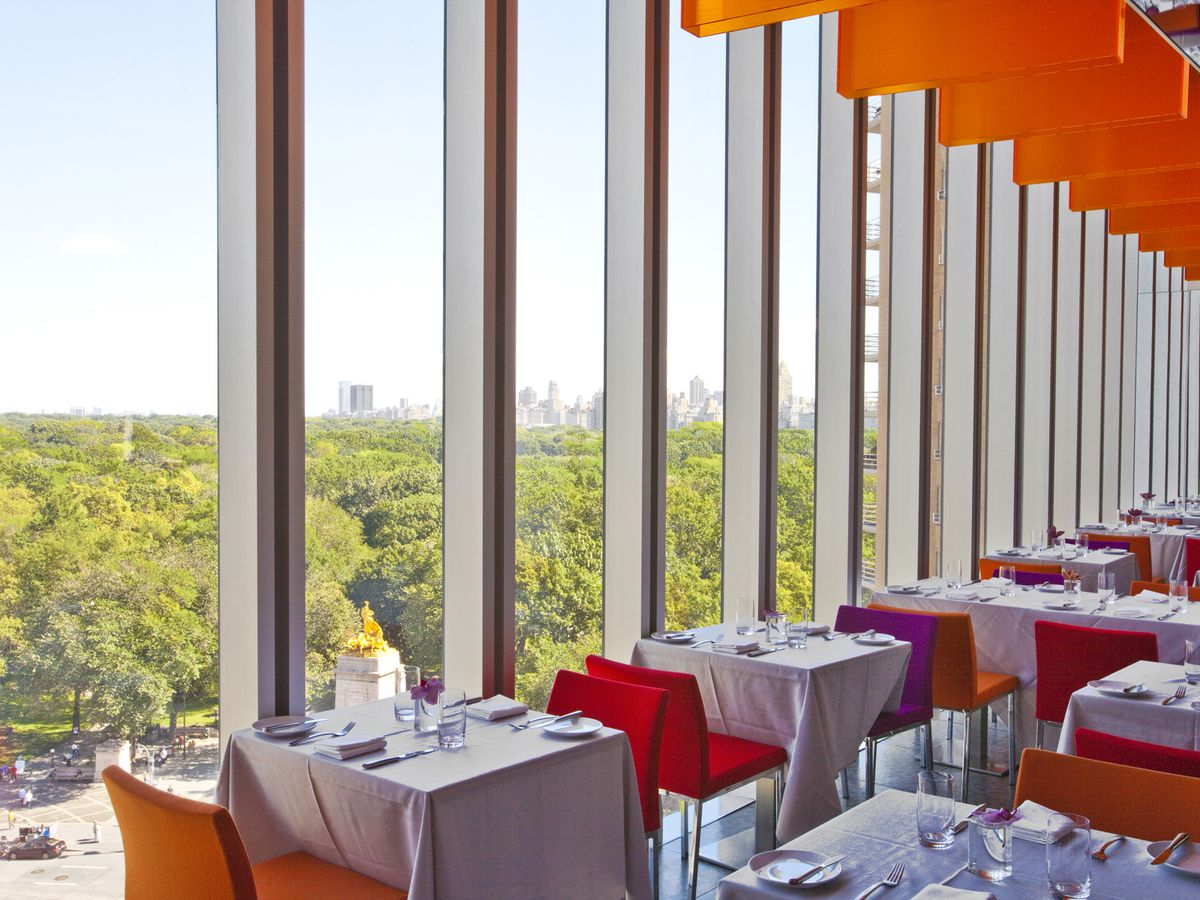 Orange chairs are pulled up to white tablecloth tables in a restaurant that offers views of a park through floor-to-ceiling windows