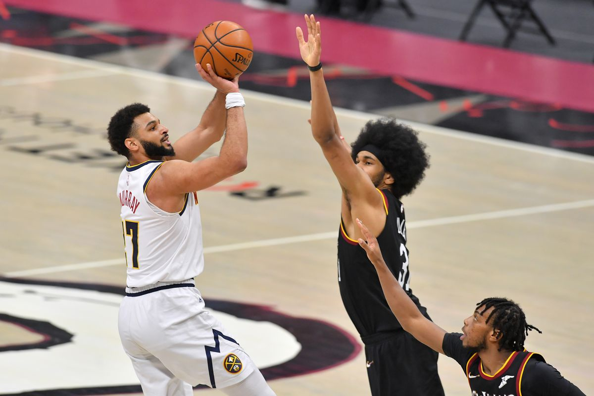 Jamal Murray of the Denver Nuggets shoots over Jarrett Allen and Darius Garland of the Cleveland Cavaliers during the fourth quarter at Rocket Mortgage Fieldhouse on February 19, 2021 in Cleveland, Ohio.