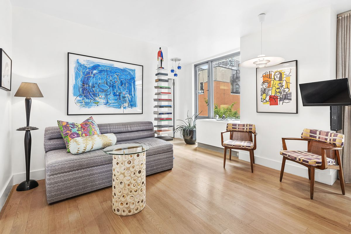 A living room with hardwood floors, a small couch, and colorful paintings on its white walls.