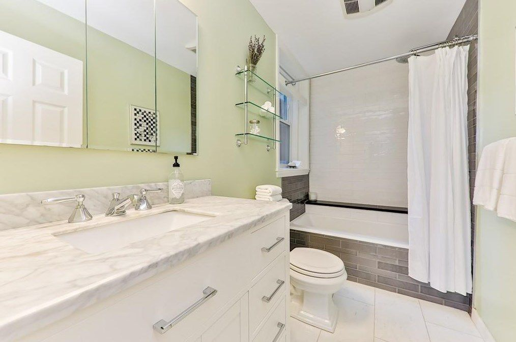 A bathroom with a long vanity ending in a shower with the curtain pulled back.