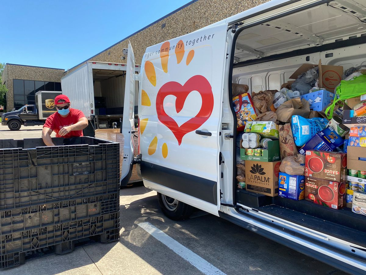 A white van with large heart logo painted on the door filled with boxes of food donations. A worker in a red t-shirt sorts those donations into a large black bin.