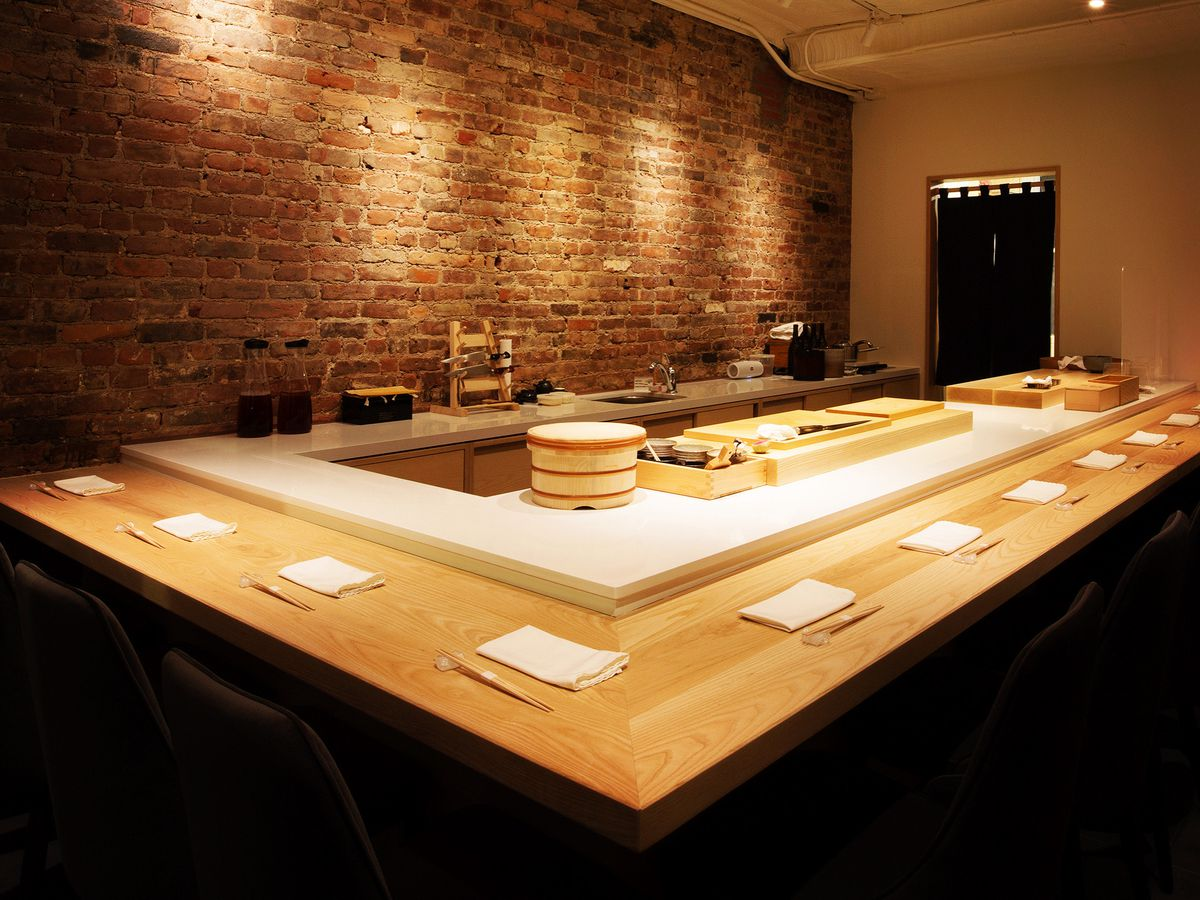 A light wood sushi counter with napkins and chopsticks set for service