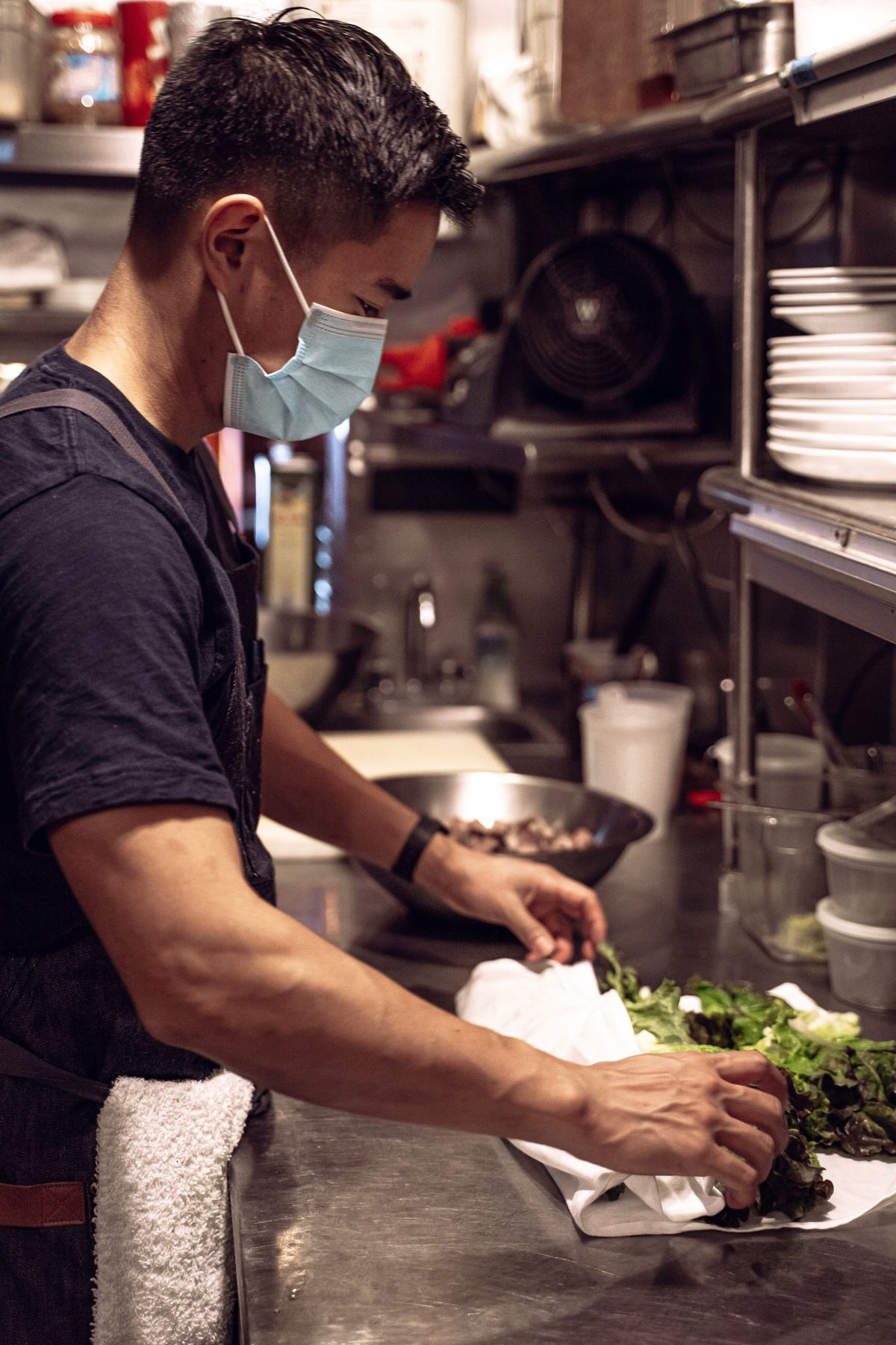 A man in a black t-shirt and disposable blue face mask stands at a restaurant kitchen counter preparing vegetables