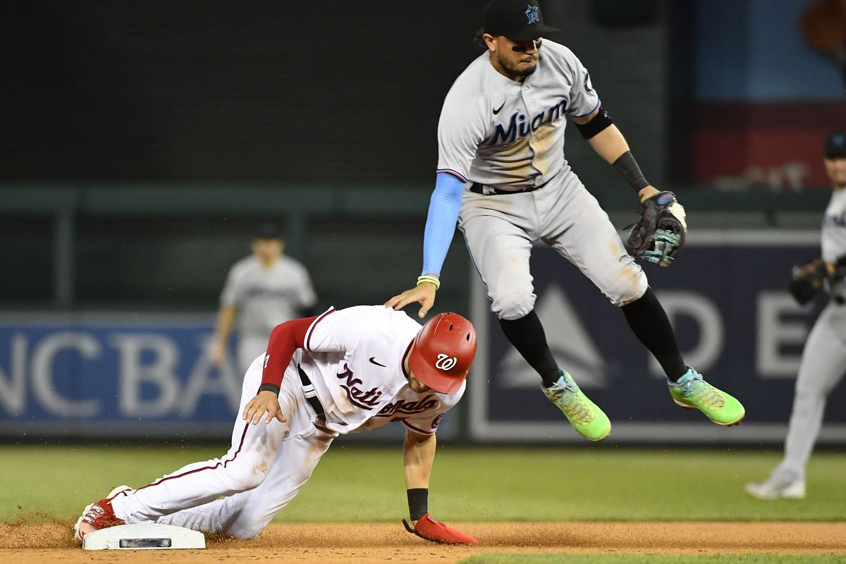 Washington Nationals shortstop Trea Turner (7) steals second base as Miami Marlins shortstop Miguel Rojas (19) leaps during the eighth inning at Nationals Park.