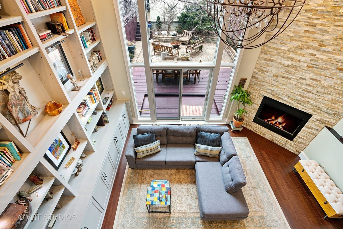 A grey L-shaped couch in next to a stone fireplace and built-in shelves with books and art. The two-story window looks out onto the deck.