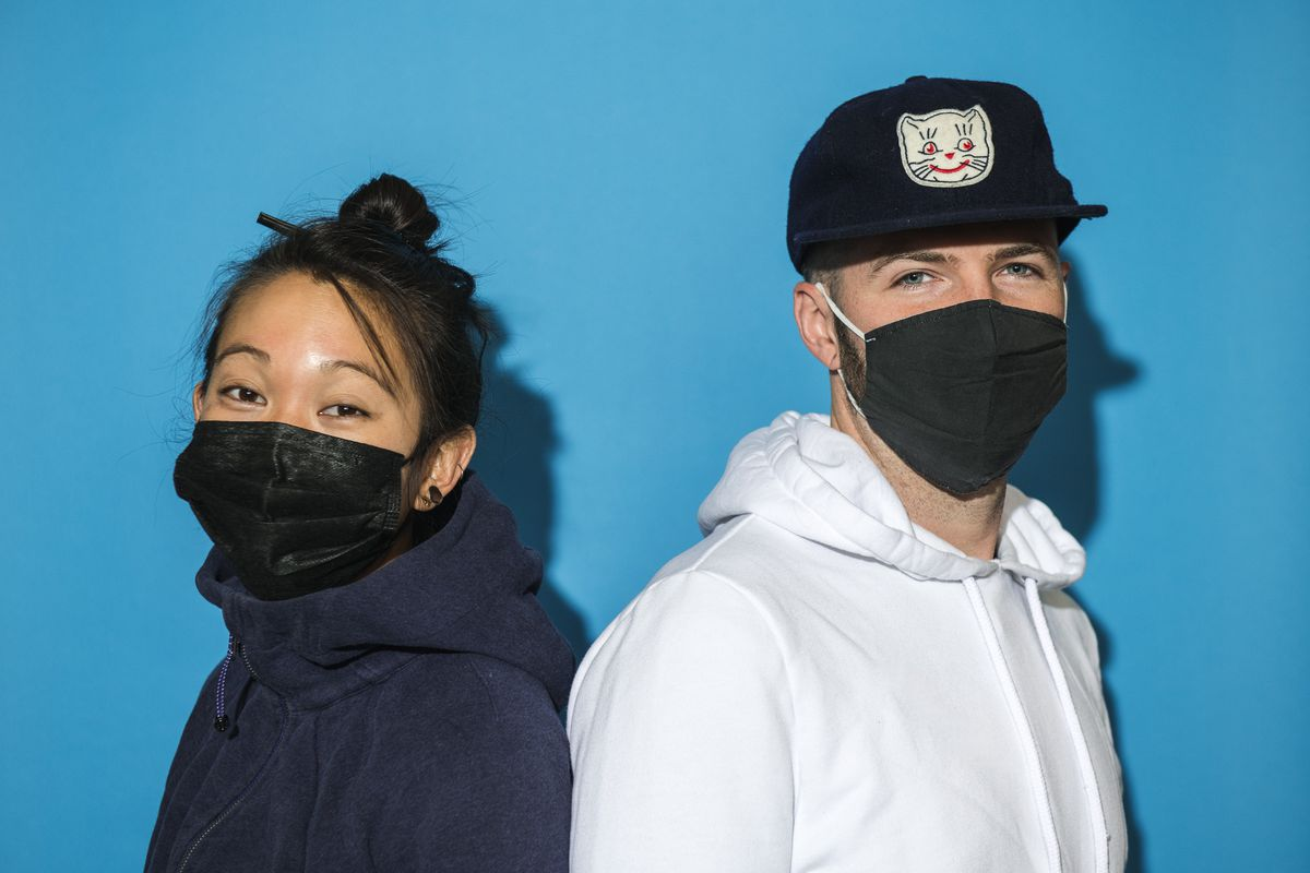 A woman and man stand back to back wearing face masks