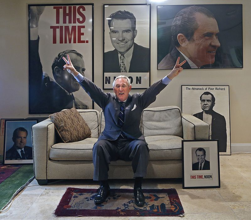 Roger Stone, making an arms-up V-for-victory gesture, is seated in a room with multiple framed pictures of Richard Nixon.