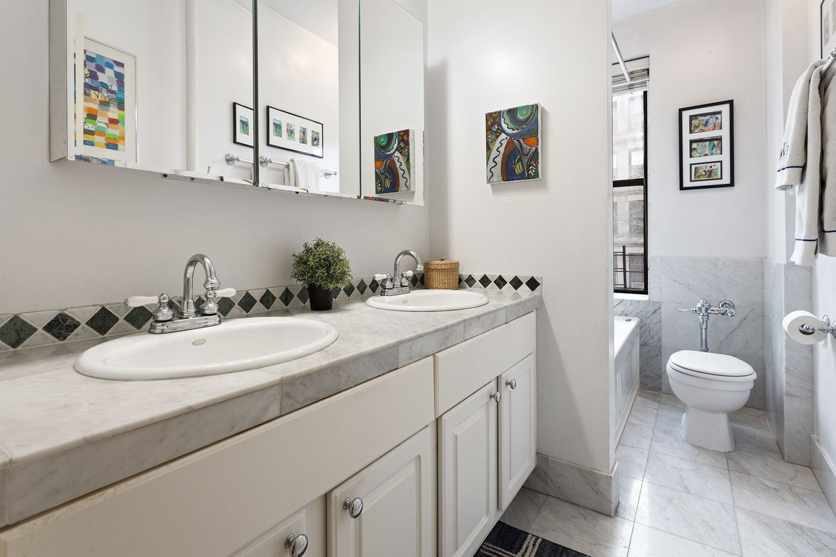 The windowed bathroom comes with a dual-sink vanity, white and gray marble tile, and a large window in the shower.