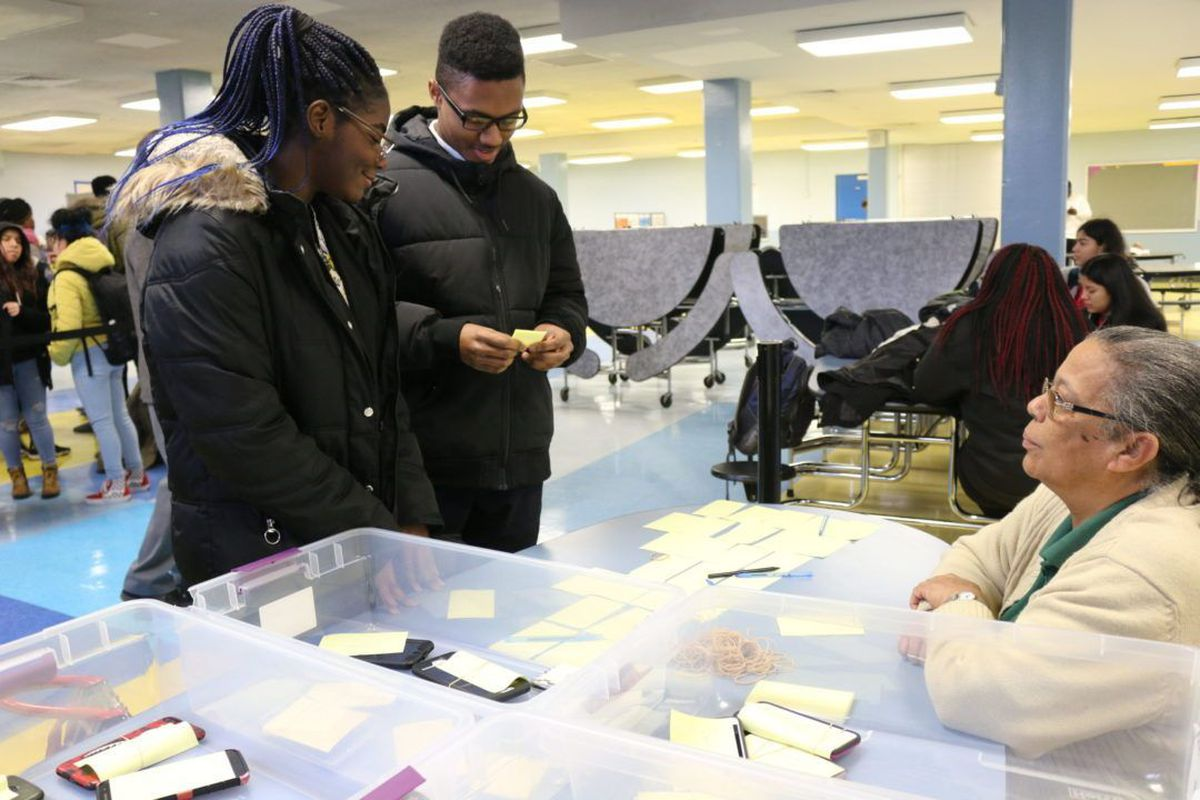 Abigail Thompson, left, and Talike Bennett turn their phones in to Eva Hunte at the Brooklyn Academy of Science and the Environment.